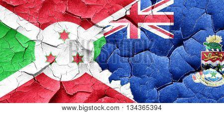 Burundi flag with Cayman islands flag on a grunge cracked wall