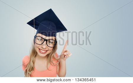 people, graduation and education concept - smiling young student woman in mortarboard and eyeglasses pointing finger up over gray background