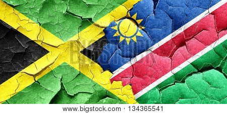 Jamaica flag with Namibia flag on a grunge cracked wall