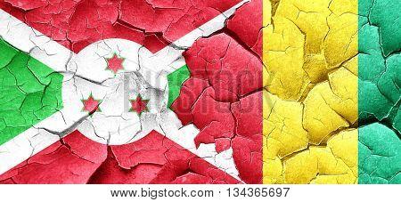 Burundi flag with Guinea flag on a grunge cracked wall