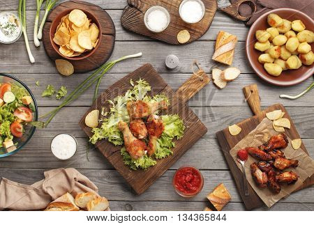 Different food on a wooden table grilled chicken legs buffalo wings salad potatoes beer and snack to beer. Outdoors Food Concept