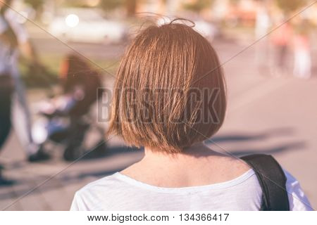 Casual young woman walking on city streets as everyday ordinary activity from behind selective focus