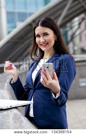 Beautiful young business woman reading a message on the phone