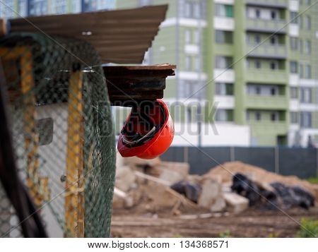 The helmet is against the background of a construction site. Completed new homes. Metal mesh fence - the fence construction