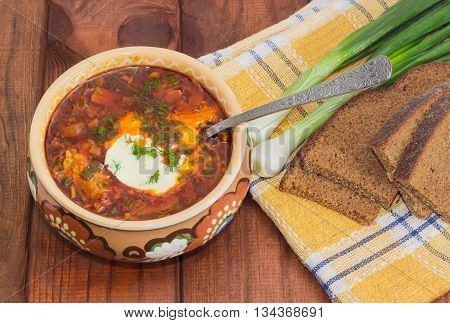 Ukrainian borscht garnished with dill and a sour cream in ceramic bowl and a spoon in it on the background of a green onions and sliced brown bread on a chequered linen cloth on wood planks closeup
