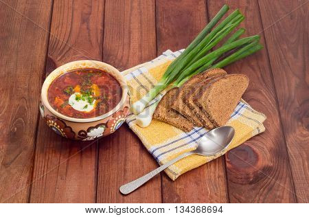 Ceramic bowl of Ukrainian borscht garnished with dill and a sour cream green onions sliced brown bread and spoon on a chequered linen cloth on wood planks