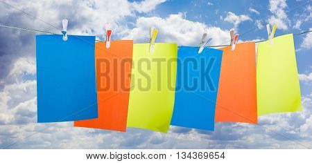 Blank sheets of colored paper fixed a plastic clothespins with colored inserts on clothesline against the sky with clouds