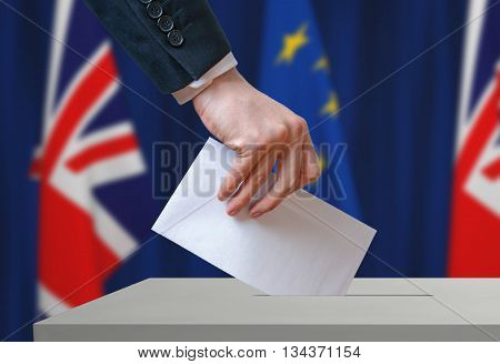 Referendum in Great Britain (Brexit) about relationship with European Union. Voter holds envelope in hand above ballot.