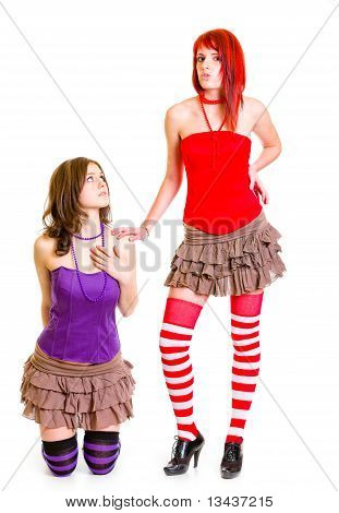 Young girl on knees pleading her strict girlfriend isolated on white