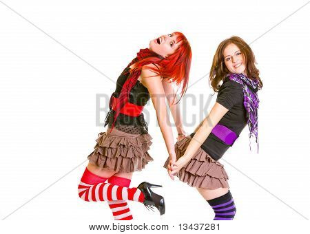 Two pretty cheerful girls standing back to back and holding hands isolated on white