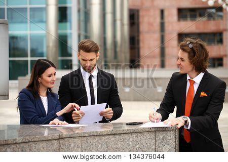 Business people sign a contract, street outdoors