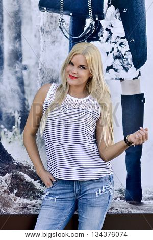 Portrait of fashionable girl.Fashionable,beautiful woman.Fashionable,beautiful model near the new brand shop,stylish,trendy model.Big shopping,sales.Girl with stylish fashionable,branded clothes.Taste