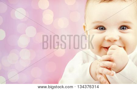 children, holidays, people, infancy and age concept - happy baby over pink lights background
