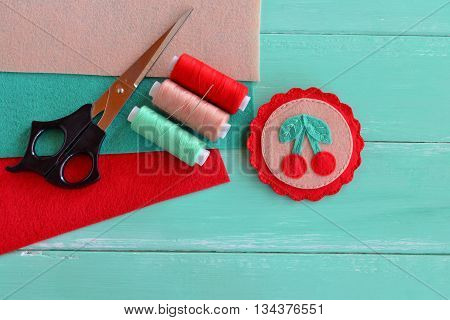 Cute felt brooch with red cherries and green leaves. Beautiful summer accessory for girls and women. Home made decoration brooch. Felt sheets thread kit, scissors, needle. Crafts supplies and tool