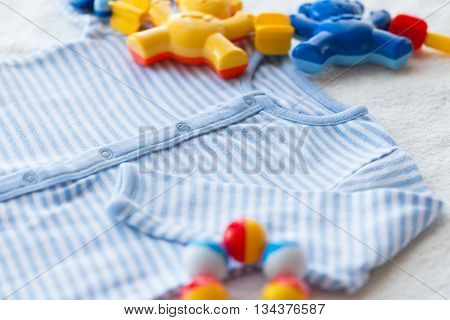 baby clothes, babyhood and object concept - close up of blue bodysuit on towel for newborn boy and rattle