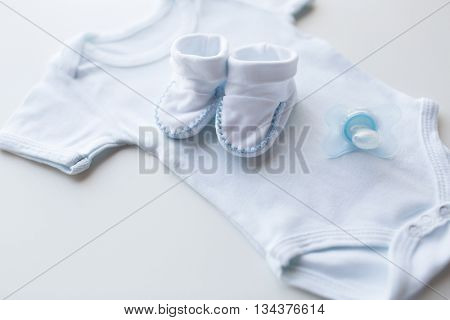 baby clothes, babyhood, motherhood and object concept - close up of white bodysuit, bootees and soother for newborn boy on table