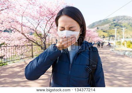 Woman suffer cough with sakura tree