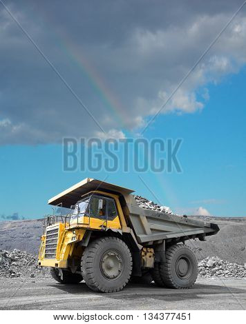 Heavy mining truck driving through the iron ore opencast. Rainbow in the sky on the background