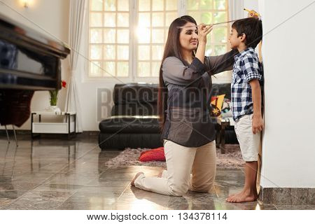 Mother checking her son's height at home