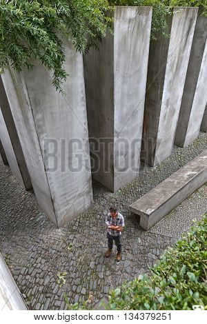 July 2015 - The Jewish Museum Berlin Berlin Germany: The Garden of Exile and Emigration.The 49th column filled with earth from Jerusalem stands for Berlin. Man reading and standing still
