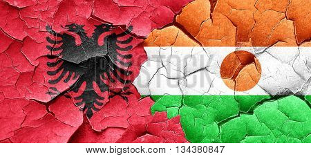 Albania flag with Niger flag on a grunge cracked wall