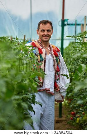 Romanian Farmer In Traditional Costume In His Greenhouse