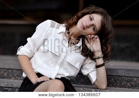 Fashionable portrait of fashionable, glamorous, beautiful, attractive, pretty, nice, gorgeous girl, student, school girl sitting on stairs near college, campus, library, university, school. Beautiful girl, study.