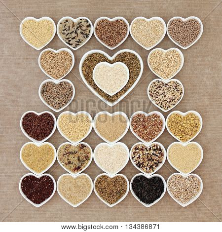 Natural grain health food in heart shaped bowls forming an abstract background.