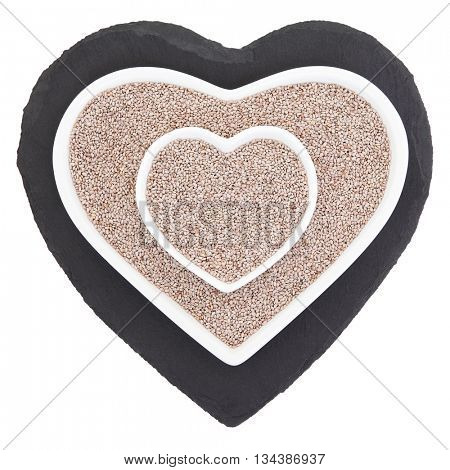 Chia seed health food in heart shaped porcelain bowls on slate over white background. Salvia hispanica.
