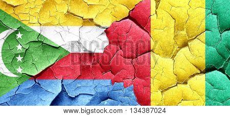Comoros flag with Guinea flag on a grunge cracked wall