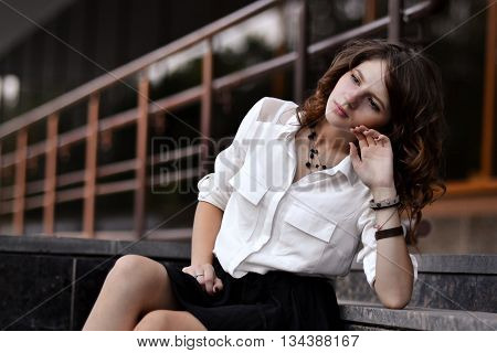 Fashionable, glamorous, attractive, beautiful, amazing, pretty, nice, awesome, gorgeous girl, student, school girl sitting on stairs near school, university, campus, library. Sad, sorrowful girl think about study