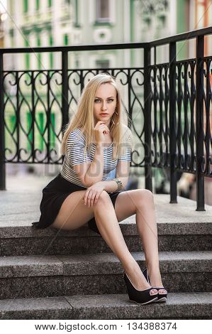 Beautiful blonde woman at the colorful summer city in the striped t-shirt posing on the stairs - photo with shallow dept of field