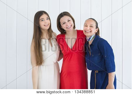 Happy female friends with pregnant woman on white background
