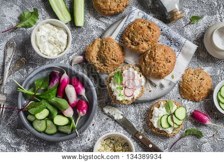 Homemade whole grain rolls cottage cheese fresh vegetables - radishes cucumbers lettuce and sandwiches with cheese radish and cucumber on a grey stone background. Healthy snack in a rustic style. Top view