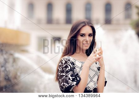 Beautiful Girl with Champagne Glass Celebrating by the Fountain