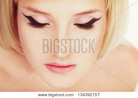 Vintage style portrait of young beautiful girl with fancy cat eye make-up