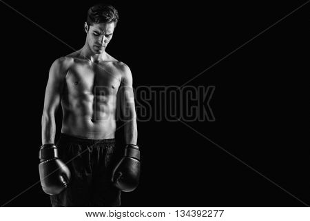 Boxer posing after failure against black background