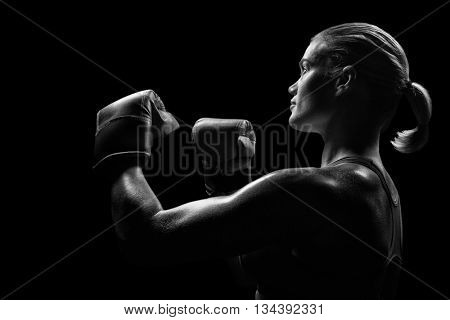 Side view of female boxer with fighting stance against black background