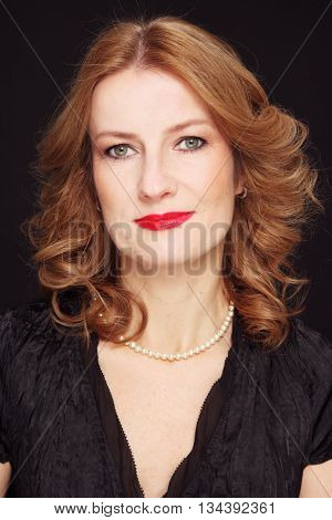 Portrait of beautiful happy smiling mature woman with curly hair and red lipstick