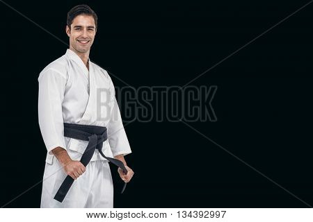 Fighter tightening karate belt against black background