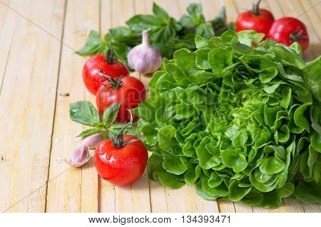 Fresh lettuce tomato, basil and garlic for a light summer salad on a wooden surface, selective focus