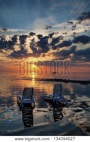 Two empty striped deck chairs with a shadow in the water of the Baltic Sea beach at sunset with yacht on the horizon