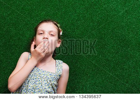 Little girl is lying on artificial grass. She is tired and needs to sleep.