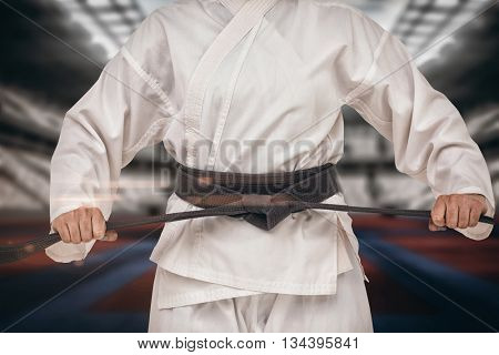 Fighter tightening karate belt against digitally generated image of stadium