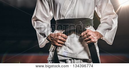 Fighter tightening karate belt against composite image of playing field indoor