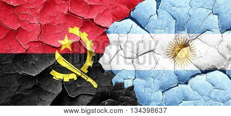 Angola flag with Argentine flag on a grunge cracked wall