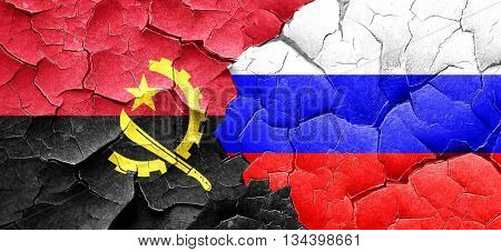 Angola flag with Russia flag on a grunge cracked wall