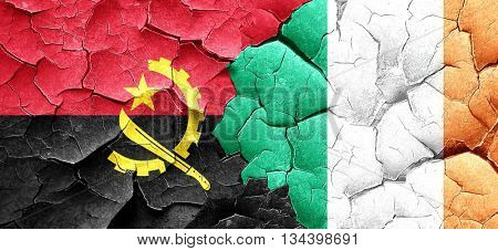 Angola flag with Ireland flag on a grunge cracked wall