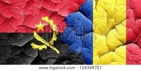 Angola flag with Romania flag on a grunge cracked wall