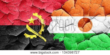 Angola flag with Niger flag on a grunge cracked wall